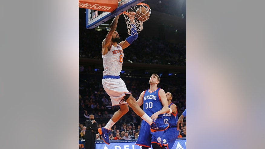 New York Knicks' Tyson Chandler (6) dunks the ball as Philadelphia 76ers' Spencer Hawes watches during the first half of an NBA basketball game Wednesday, Jan. 22, 2014, in New York. (AP Photo/Frank Franklin II)