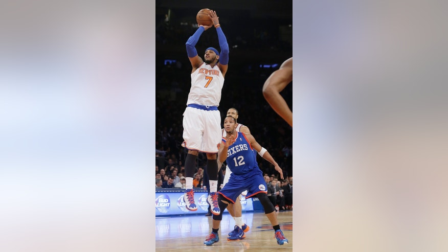 New York Knicks' Carmelo Anthony (7) shoots as Philadelphia 76ers' Evan Turner (12) looks on during the first half of an NBA basketball game, Wednesday, Jan. 22, 2014, in New York.  (AP Photo/Frank Franklin II)