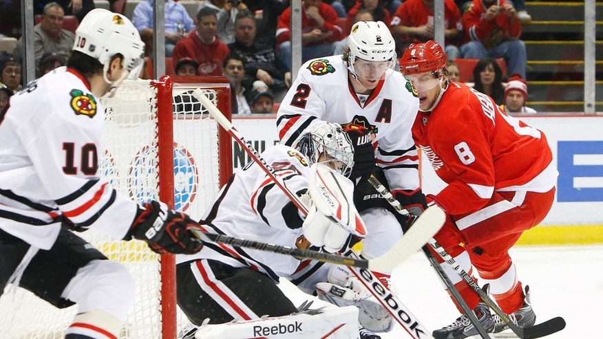 Chicago Blackhawks goalie Corey Crawford, second from left, stops a Detroit Red Wings left wing Justin Abdelkader's (8) shot in the second period of an NHL hockey game Wednesday, Jan. 22, 2014, in Detroit. (AP Photo/Paul Sancya)