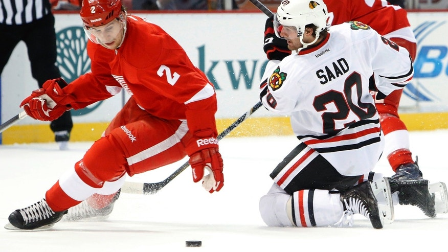 Chicago Blackhawks left wing Brandon Saad (20) loses the puck to Detroit Red Wings defenseman Brendan Smith (2) in the first period of an NHL hockey game Wednesday, Jan. 22, 2014, in Detroit. (AP Photo/Paul Sancya)