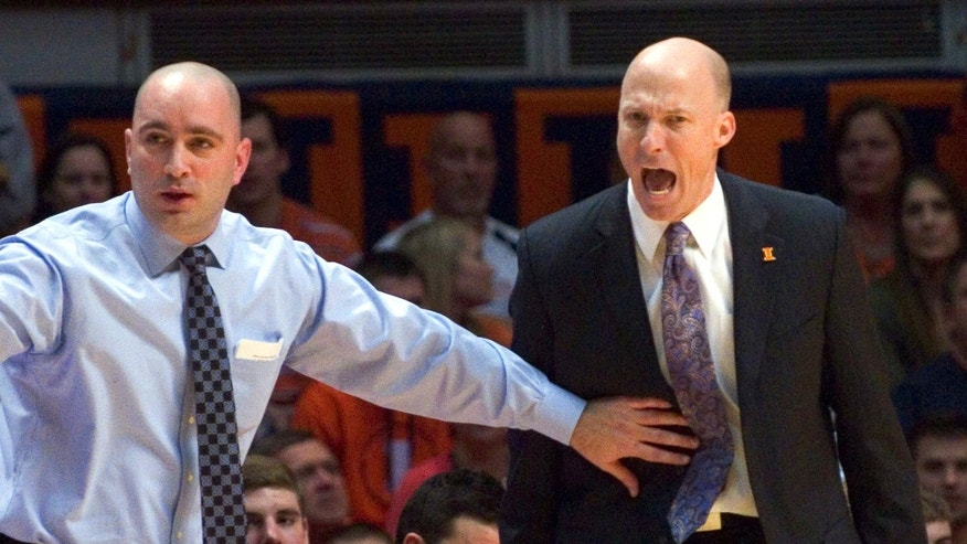 FILE - In this Jan. 18, 2014 file photo, Illinois head coach John Groce is held back by assistant coach Dustin Ford as Groce argues a call during Illinois' 78-62 loss to Michigan State in an NCAA college basketball game in Champaign, Ill. Groce said Wednesday, Jan. 22, 2014, that he went too far in a series of outbursts during the loss. (AP Photo/Robin Scholz, File)