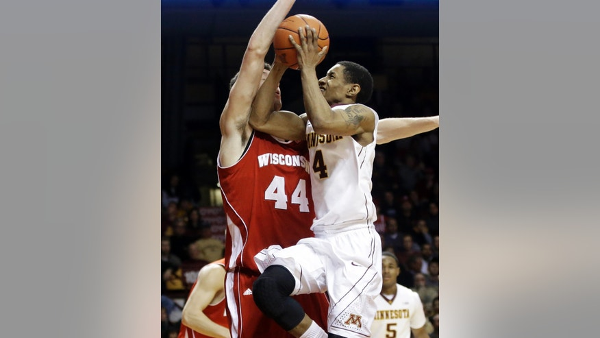 Minnesota's Deandre Mathieu, right, drives into Wisconsin's Frank Kaminsky, left, in the second half of an NCAA college basketball game, Wednesday, Jan. 22, 2014, in Minneapolis. Mathieu and Maurice Walker each scored 18 points to lead Minnesota in their 81-68 win. (AP Photo/Jim Mone)