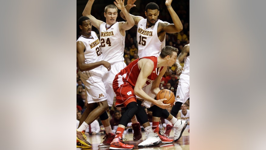 Wisconsin's Sam Dekker, lower right, gains control of the loose ball as Minnesota's Austin Hollins, left, Joey King, center, and Maurice Walker defend in the first half of an NCAA college basketball game against Wisconsin, Wednesday, Jan. 22, 2014, in Minneapolis.   (AP Photo/Jim Mone)