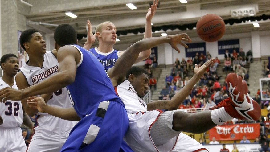 The ball gets away as Duquesne's Ovie Soko, right, and Saint Louis' Dwayne Evans, left, and John Manning, center, chase a rebound during the first half of an NCAA college basketball game on Wednesday, Jan. 22, 2014, in Pittsburgh. (AP Photo/Keith Srakocic)