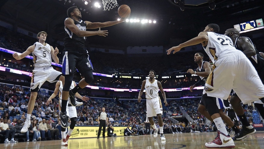 Sacramento Kings small forward Rudy Gay (8) goes to the basket between New Orleans Pelicans center Jeff Withey (5), small forward Al-Farouq Aminu (0), and power forward Anthony Davis (23) in the second half of an NBA basketball game in New Orleans, Tuesday, Jan. 21, 2014.  The Kings won 114-97. (AP Photo/Gerald Herbert)