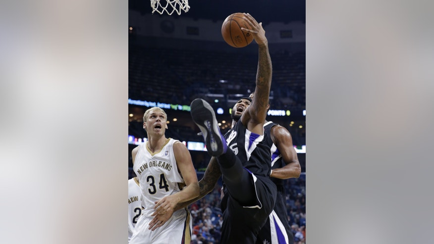 Sacramento Kings center DeMarcus Cousins pulls down an offensive rebound in front of New Orleans Pelicans center Greg Stiemsma (34) in the first half of an NBA basketball game in New Orleans, Tuesday, Jan. 21, 2014. (AP Photo/Gerald Herbert)