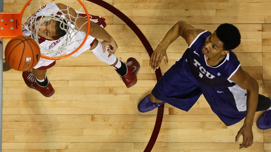 Oklahoma forward D.J. Bennett, left, shoots in front of TCU center Karviar Shepherd during the first half of an NCAA college basketball game in Norman, Okla., Wednesday, Jan. 22, 2014. (AP Photo/Sue Ogrocki)