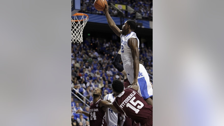 Kentucky's Alex Poythress, top, dunks over Texas A&M's Davonte Fitzgerald (15) and Antwan Space (24) during the second half of an NCAA college basketball game, Tuesday, Jan. 21, 2014, in Lexington, Ky. Kentucky won 68-51. (AP Photo/James Crisp)