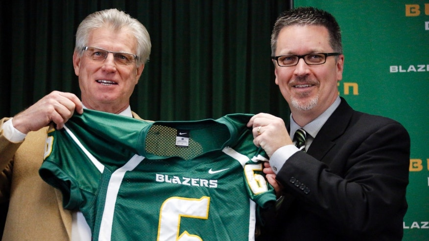 New Belhaven University football coach, left, and athletic director Scott Little hold up a football jersey after Mumme was introduced during an NAIA college football nbews conference in Jackson, Miss., Tuesday, Jan. 21, 2014. Mumme, a former head coach at a number of programs including Division 1 schools, Kentucky and New Mexico State University, most recently was passing game coordinator at SMU. (AP Photo/Rogelio V. Solis)