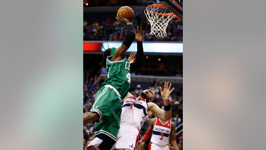 Washington Wizards center Marcin Gortat (4), from Poland, draws the charging foul from Boston Celtics forward Gerald Wallace (45) in the first half of an NBA basketball game, Wednesday, Jan. 22, 2014, in Washington. (AP Photo/Alex Brandon)