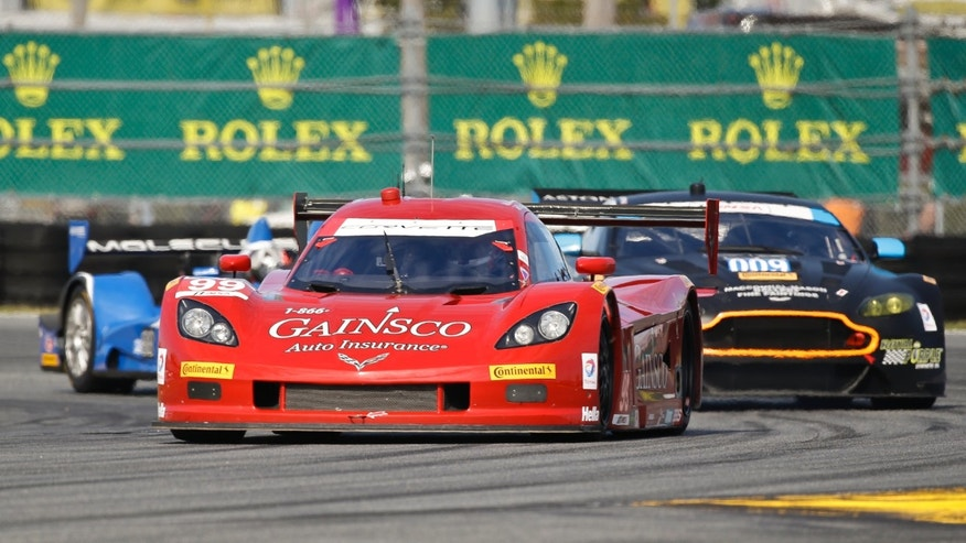Alex Gureny, front, passes several cars as he drives the GAINSCO Corvette DP through a horseshoe turn during practice for the IMSA Series Rolex 24 hour auto race at Daytona International Speedway in Daytona Beach, Fla., Thursday, Jan. 23, 2014.(AP Photo/John Raoux)