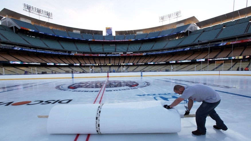 A worker rolls up mylar that protected a hockey rink at Dodger Stadium from daytime temperatures in the high 70s Fahrenheit, as preparations continue for the upcoming 2014 NHL Stadium Series hockey game in Los Angeles, Wednesday, Jan. 22, 2014. The Los Angeles Kings and Anaheim Ducks will play outdoors at Dodger Stadium next Saturday, Jan. 25th. (AP Photo/Nick Ut)