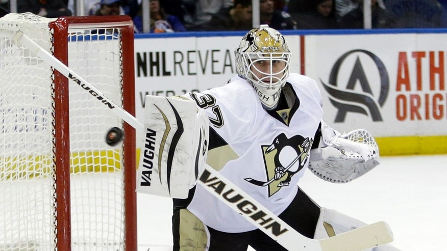 Pittsburgh Penguins goalie Jeff Zatkoff (37) stops a shot on the goal during the second period of an NHL hockey game against the New York Islanders, Thursday, Jan. 23, 2014, in Uniondale, N.Y. (AP Photo/Frank Franklin II)