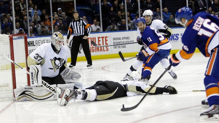 Pittsburgh Penguins goalie Jeff Zatkoff (37) stops a shot on goal by New York Islanders' Peter Regin (16) during the second period of an NHL hockey game, Thursday, Jan. 23, 2014, in Uniondale, N.Y. (AP Photo/Frank Franklin II)
