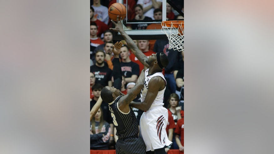 Cincinnati forward Justin Jackson, right, blocks a shot by Central Florida guard Isaiah Sykes in the first half of an NCAA college basketball game, Thursday, Jan. 23, 2014, in Cincinnati. (AP Photo/Al Behrman)
