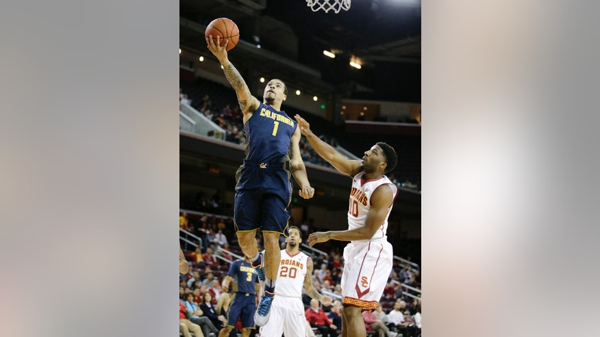 California's Justin Cobbs, left, goes up for a basket as Southern California's Pe'Shon Howard watches during the first half of an NCAA college basketball game Wednesday, Jan. 22, 2014, in Los Angeles. (AP Photo/Jae C. Hong)