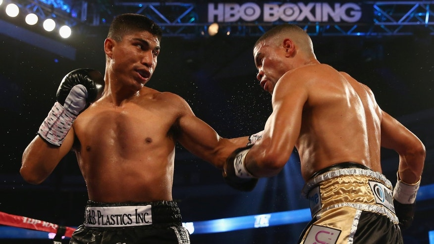 DALLAS, TX - JUNE 15:  (L-R) Mikey Garcia connects with a left to the face of Juan Manuel Lopez during their Vacant WBO Featherweight Title bout at American Airlines Center on June 15, 2013 in Dallas, Texas. Garcia knocked out Lopez in the fourth round.  (Photo by Tom Pennington/Getty Images)