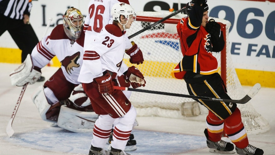 Phoenix Coyotes goalie Mike Smith, Michael Stone, left to right, Oliver Ekman-Larsson, from Sweden, look on as Calgary Flames' Lance Bouma celebrates his goal during second period NHL hockey action in Calgary, Canada, Wednesday, Jan. 22, 2014. (AP Photo/The Canadian Press, Jeff McIntosh)