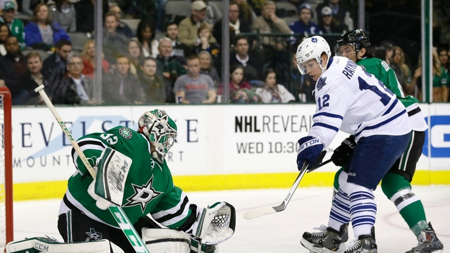 Dallas Stars goalie Kari Lehtonen (32) of Finland stops a shot with his leg pad as Toronto Maple Leafs' Mason Raymond (12) looks for a rebound during the second period of an NHL hockey game, Thursday, Jan. 23, 2014, in Dallas. The Stars' Brenden Dillon is at rear. (AP Photo/Tony Gutierrez)