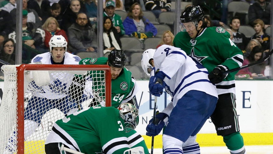 Dallas Stars' Kari Lehtonen (32), of Finland, attempts to glove the puck as Toronto Maple Leafs' Joffrey Lupul (19) looks for a scoring opportunity during the second period of an NHL hockey game, Thursday, Jan. 23, 2014, in Dallas. Stars' Brenden Dillon is at right. (AP Photo/Tony Gutierrez)