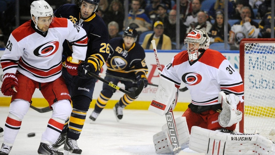 Carolina Hurricanes defenseman John-Michael Liles (26) battles with Buffalo Sabres left winger Matt Moulson (26) as goaltender Anton Khudobin (31), of Russia, eyes the incoming puck during the first period of an NHL hockey game in Buffalo, N.Y., Thursday, Jan. 23, 2014. (AP Photo/Gary Wiepert)