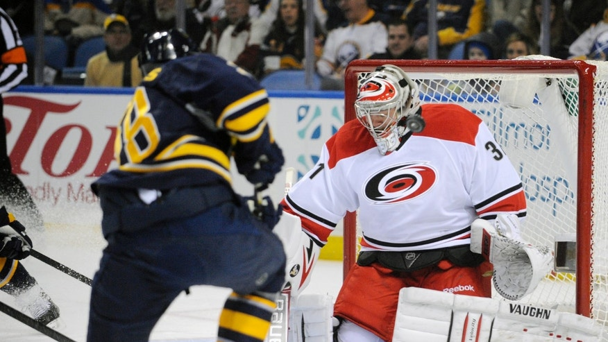 Buffalo Sabres' Zemgus Girgensons (28), of Latvia, shoots the puck off the mask of  Carolina Hurricanes' Anton Khudobin (31), of Russia, during the first period of an NHL hockey game in Buffalo, N.Y., Thursday, Jan. 23, 2014. (AP Photo/Gary Wiepert)