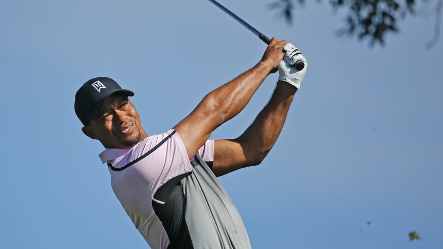 Tiger Woods watches his tee shot on the par-3 third hole on the South Course at Torrey Pines during the first round of the Farmers Insurance Open golf tournament Thursday, Jan. 23, 2014, in San Diego. Woods made par on the hole. (AP Photo/Lenny Ignelzi)