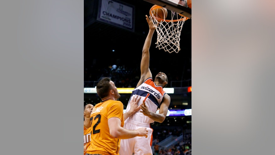 Washington Wizards' Trevor Ariza (1) scores in front of Phoenix Suns' Miles Plumlee, left, during the first half of an NBA basketball game, Friday, Jan. 24, 2014, in Phoenix. (AP Photo/Ross D. Franklin)