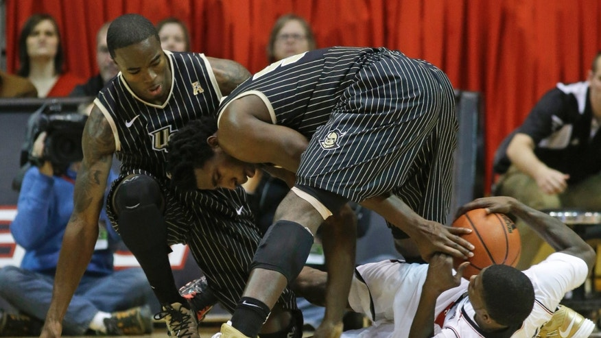 Central Florida forward Staphon Blair, center, reaches for a loose ball against Cincinnati forward Shaquille Thomas, right, in the second half of an NCAA college basketball game, Thursday, Jan. 23, 2014, in Cincinnati. Guard Isaiah Sykes watches at left. Cincinnati won 69-51. (AP Photo/Al Behrman)