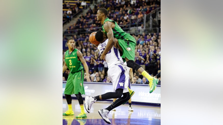 Oregon' Elgin Cook, right, fouls Washington's C.J. Wilcox as Oregon's Joseph Young (3) looks on in the first half of an NCAA men's college basketball game Thursday, Jan. 23, 2014, in Seattle. (AP Photo/Elaine Thompson)