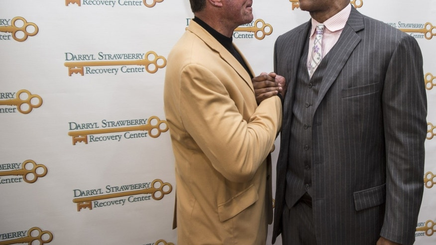 Retired NFL football player Jack Youngblood, left, talks with retired baseball player Darryl Strawberry at the grand opening event for the Darryl Strawberry Recovery Center in St. Cloud, Fla., Friday, Jan. 24, 2014. The center features a program aimed at helping athletes address post-playing issues. (AP Photo/Willie J. Allen Jr.)