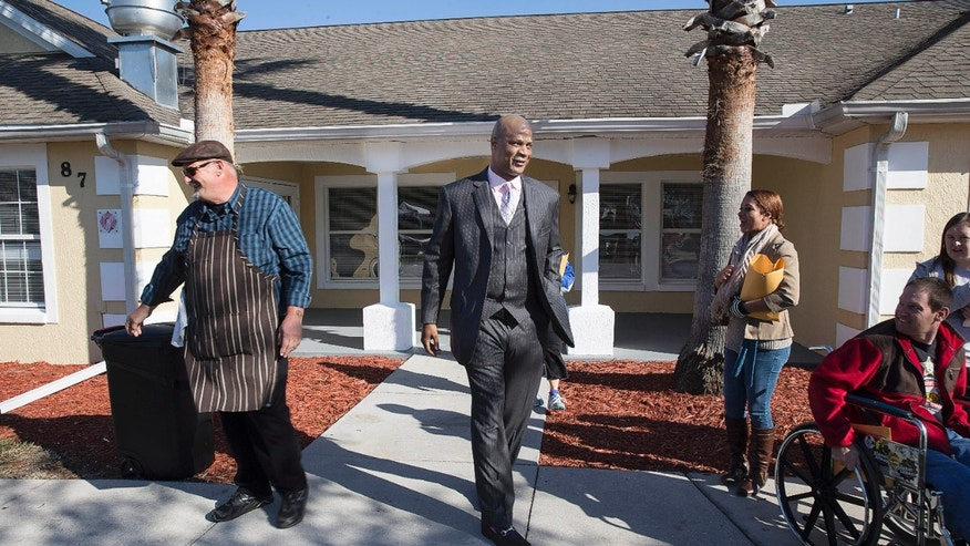 Food service manager Frank Mussolini, left, laughs after a quick conversation with retired baseball player Darryl Strawberry, center, in front of a recovery unit at the grand opening of the Darryl Strawberry Recovery Center in St. Cloud, Fla., Friday, Jan. 24, 2014. The center features a program aimed at helping athletes address post-playing issues. (AP Photo/Willie J. Allen Jr.)