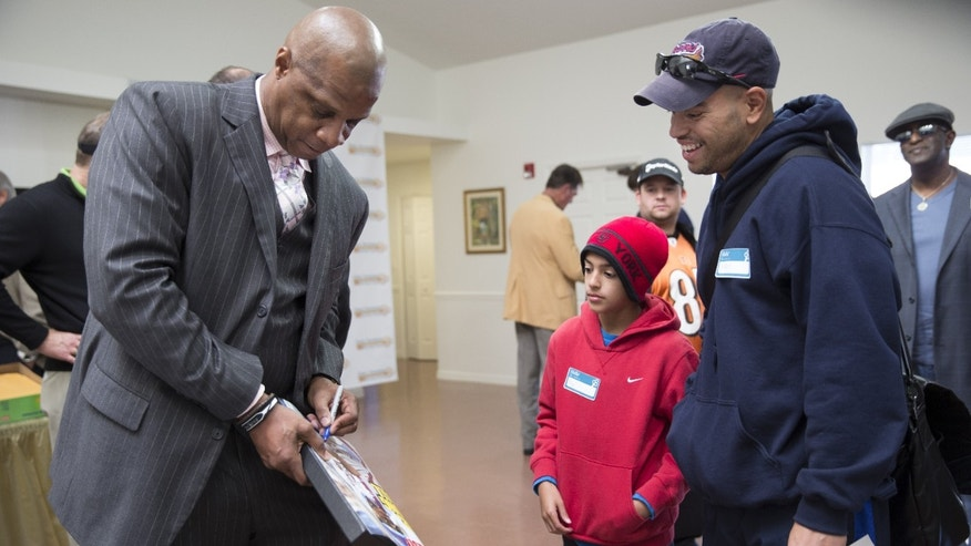 Retired baseball player Darryl Strawberry, left, signs autographs for Angel Alvarez, 10, center and his father Gilbert Alvarez, right, at the grand opening event for the Darryl Strawberry Recovery Center in St. Cloud, Fla., Friday, Jan. 24, 2014. The center features a program aimed at helping athletes address post-playing issues. (AP Photo/Willie J. Allen Jr.)