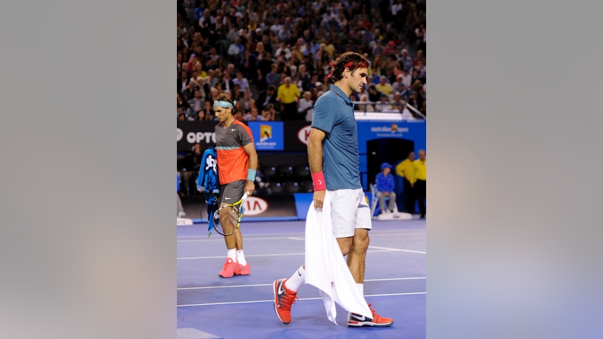 Roger Federer of Switzerland, right, and  Rafael Nadal of Spain walk during the change of end in their semifinal at the Australian Open tennis championship in Melbourne, Australia, Friday, Jan. 24, 2014. (AP Photo/Andrew Brownbill)