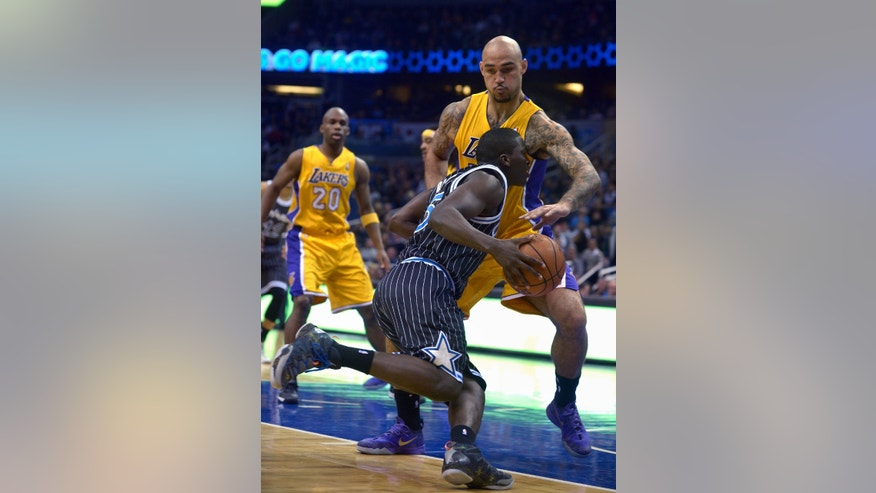 Orlando Magic guard Victor Oladipo (5) is fouled by Los Angeles Lakers center Robert Sacre, while driving to the basket, as Jodie Meeks (20) watches during the first half of an NBA basketball game in Orlando, Fla., Friday, Jan. 24, 2014. (AP Photo/Phelan M. Ebenhack)