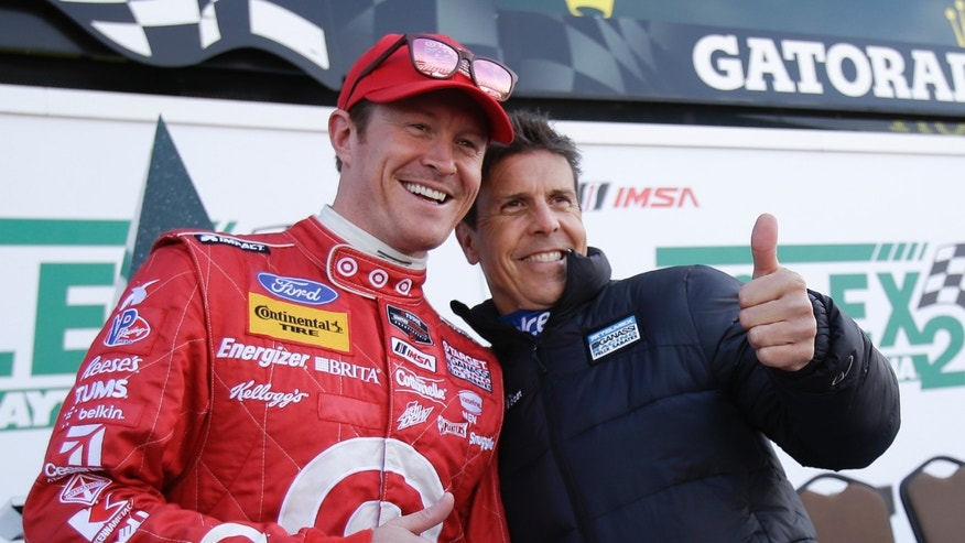 Drivers Scott Dixon, left of New Zealand, and Scott Pruett pose for photographers after a practice session for the IMSA Series Rolex 24 hour auto race at Daytona International Speedway in Daytona Beach, Fla., Friday, Jan. 24, 2014.(AP Photo/John Raoux)