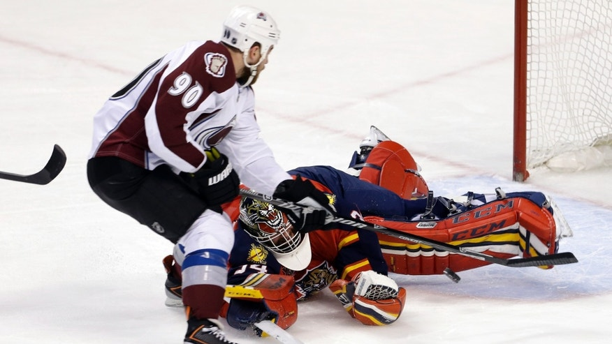 Florida Panthers goalie Tim Thomas (34) blocks a shot by Colorado Avalanche center Ryan O'Reilly (90) during the first period of an NHL hockey game in Sunrise, Fla., Friday, Jan. 24, 2014. (AP Photo/Alan Diaz)