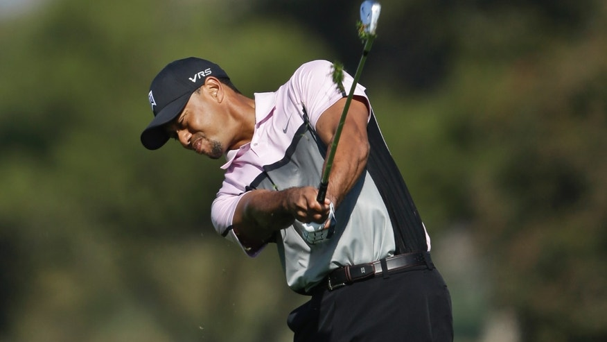 Tiger Woods digs a huge divot while hitting his approach shot to the second green on the South Course at Torrey Pines during the first round of the Farmers Insurance Open golf tournament Thursday, Jan. 23, 2014, in San Diego. (AP Photo/Lenny Ignelzi)