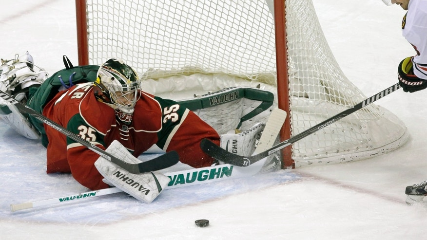 Minnesota Wild goalie Darcy Kuemper, left,  stops a shot by Chicago Blackhawks' Michal Handzus of Slovakia in the first period of an NHL hockey game, Thursday, Jan. 23, 2014, in St. Paul, Minn. (AP Photo/Jim Mone)