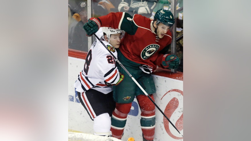 Chicago Blackhawks' Ben Smith, left, gets caught under the arm of Minnesota Wild's Marco Scandella in the first period of an NHL hockey game, Thursday, Jan. 23, 2014, in St. Paul, Minn. (AP Photo/Jim Mone)