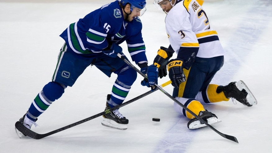 Vancouver Canucks' Brad Richardson, left, gets the puck past Nashville Predators' Seth Jones during second period NHL hockey action in Vancouver, The Tribune (of San Luis Obispo)