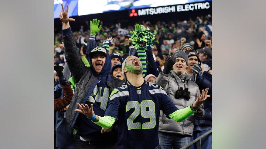ADVANCE FOR WEEKEND EDITIONS, JAN. 25-26 - In this Jan. 19, 2014, file photo, Seattle Seahawks fans celebrate a Seahawks touchdown run by Marshawn Lynch during the second half of the NFC championship NFL football game against the San Francisco 49ers in Seattle. The last time one of Seattle's major franchises had a parade to celebrate a title, no one on the Seahawks roster was born. To call Seattle's championship history thin is an understatement. Maybe that's why there's so much support behind these Super Bowl-bound Seahawks. (AP Photo/Elaine Thompson, File)