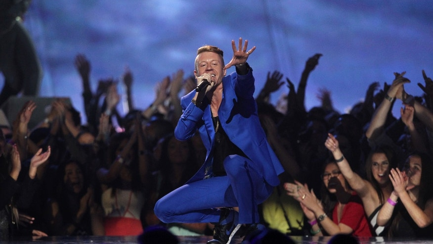 "FILE - In this April 14, 2013 file photo, Macklemore performs ""Can't Hold Us"" at the MTV Movie Awards in Sony Pictures Studio Lot in Culver City, Calif. Macklemore & Ryan Lewis are top contenders at the Jan. 26, 2014, Grammy Awards, with seven nominations, including best new artist and song of the year for ""Same Love."" Their debut album, ""The Heist,"" is up for album of the year and best rap album, while the massive hit ""Thrift Shop"" is nominated for best rap song and rap performance. The duo's other hit, ""Can't Hold Us,"" will compete for best music video. (Photo by Matt Sayles/Invision /AP)"