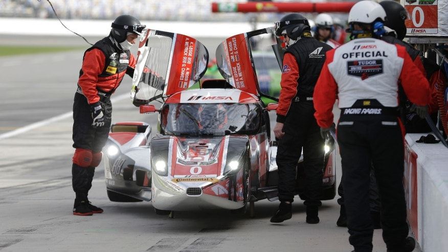 The crew of the DeltaWing DWC13 make adjustments during a pit stop at practice for the IMSA Series Rolex 24 hour auto race at Daytona International Speedway in Daytona Beach, Fla., Thursday, Jan. 23, 2014. (AP Photo/John Raoux)
