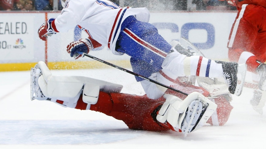 Detroit Red Wings goalie Jonas Gustavsson (50), of Sweden, stops a Montreal Canadiens center Tomas Plekanec (14), of the Czech Republic, breakaway in the first period of an NHL hockey game, Friday, Jan. 24, 2014, in Detroit. (AP Photo/Paul Sancya)