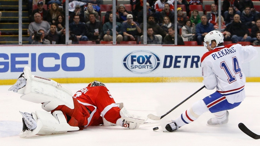 Detroit Red Wings goalie Jonas Gustavsson, left, of Sweden, stops a Montreal Canadiens center Tomas Plekanec (14), of the Czech Republic, breakaway in the first period of an NHL hockey game, Friday, Jan. 24, 2014, in Detroit. (AP Photo/Paul Sancya)