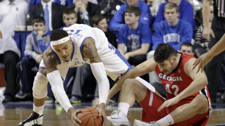 Kentucky's Willie Cauley-Stein, left, gathers up a loose ball next to Georgia's Nemanja Djurisic during the first half of an NCAA college basketball game, Saturday, Jan. 25, 2014, in Lexington, Ky. (AP Photo/James Crisp)