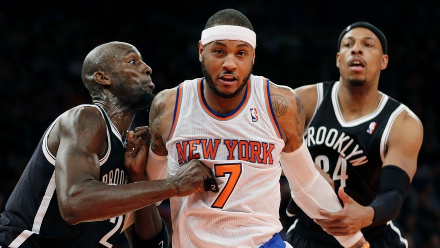New York Knicks' Carmelo Anthony, center, fights with Brooklyn Nets' Kevin Garnett, left, and Paul Pierce for a rebound during the first half of the NBA basketball game at Madison Square Garden Monday, Jan. 20, 2014, in New York. (AP Photo/Seth Wenig)