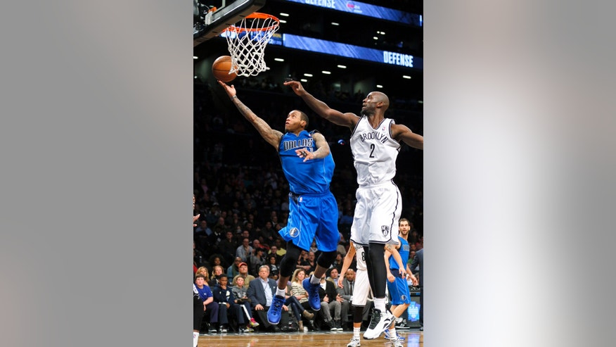 Dallas Mavericks shooting guard Monta Ellis (11) lays up a basket in the second half of an NBA basketball game as Brooklyn Nets power forward Kevin Garnett (2) tries to defend on Friday, Jan. 24, 2014, in New York. The Nets won 107 to 106. (AP Photo/Paul J. Bereswill)