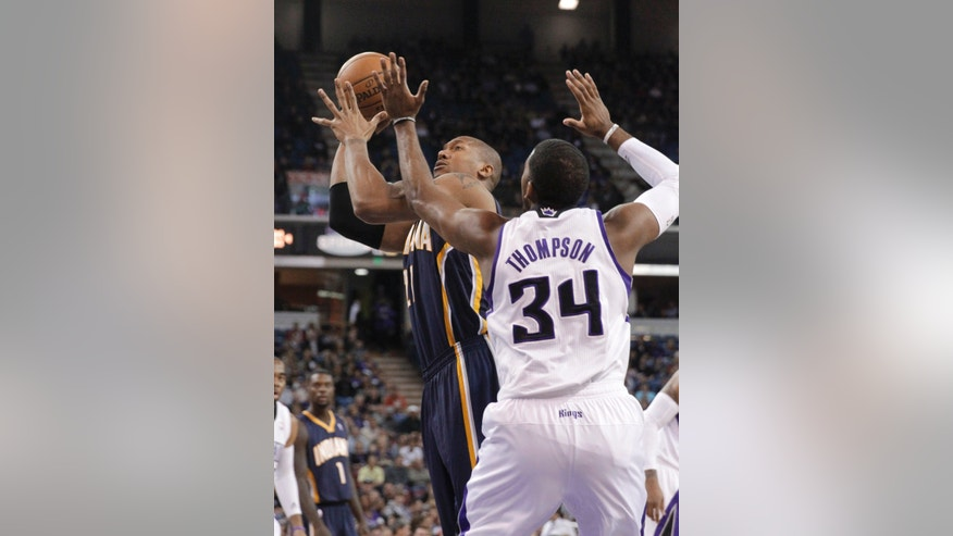 Indiana Pacers forward David West, left,  goes to the basket against Sacramento Kings forward Jason Thompson during the first quarter of an NBA basketball game in Sacramento, Calif., Friday, Jan. 24, 2014. (AP Photo/Rich Pedroncelli)